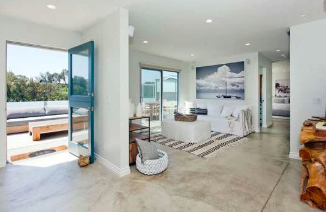 White-walled, floor-tiled living room of a $4 million manufactured home in Paradise Cove Living in Malibu. California.